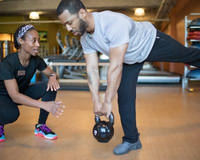Man Lifting a Kettlebell With a Personal Trainer | Colorado Athletic Club - Boulder