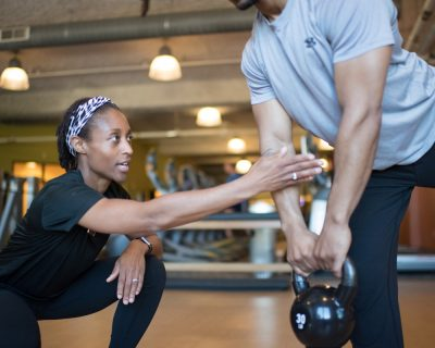 Personal Trainer Coaching Man to Use a Kettlebell | Colorado Athletic Club - DTC