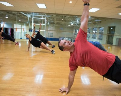 Group Fitness Class Holding a Side Plank | Colorado Athletic Club - Flatirons